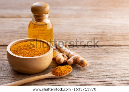 Tumeric ( curcumin, curcuma longa Linn) powder in wooden bowl and  spoon with root and bottle of turmeric essential oil extracted isolated on old wood table background. Beauty and spa concept. #1633713970