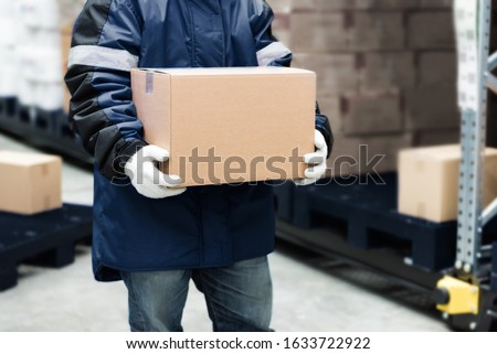 Worker carrying a goods box in a large frozen warehouse.Export-Import Logistics system concept. Royalty-Free Stock Photo #1633722922