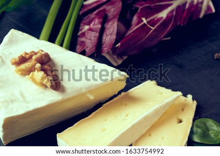 Cheese camembert or brie with rosemary and pepper on dark stone background. Copy space. Studio photo Royalty-Free Stock Photo #1633754992