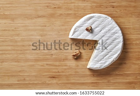 camambert cheese with nuts and basil on wooden cutting board. Royalty-Free Stock Photo #1633755022