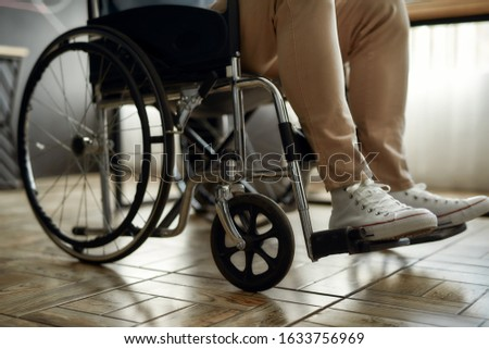 Cropped photo of male office worker in a wheelchair. Disabled man sitting on wheelchair in office. Handicapped worker. Disability and handicap concept. Unrecognizable person #1633756969