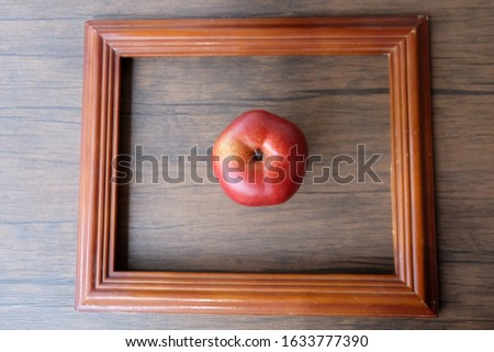 red apple in picture frame with wooden texture background