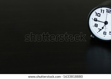 Classic clocks placed on a black table with space for placing things , selective focus. #1633818880