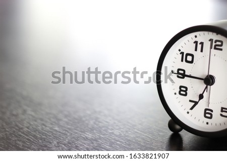 Classic clocks placed on a black table with space for placing things in the morning , selective focus. #1633821907
