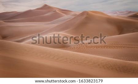 Magical Breathtaking view of a windy sand dunes deep in desert of Abu Dhabi - United Arab Emirates. Windy day in desert. Amazing dune waves. A day in desert. Desert safari.   #1633823179