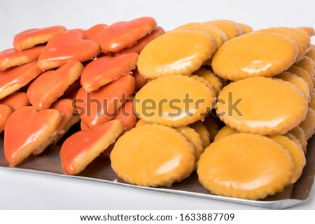 Heart-shaped and round-shaped cream pastries in a dessert tray on white background #1633887709