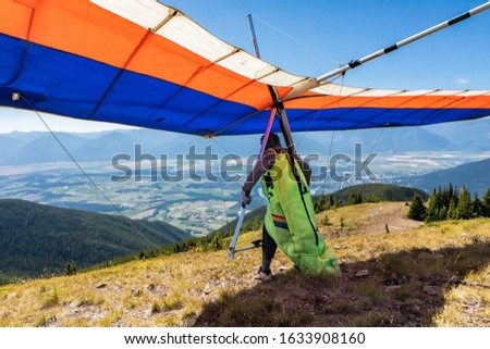 Hang glider preparing to take off from mountain top hill. Kootenay valley mountains in background, Creston, British Columbia, Canada. View from behind #1633908160