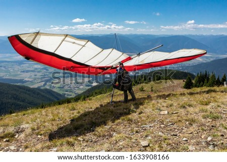 Paraglider preparing for flight from the top of mountain hill, Kootenay valley mountains in the background, Creston, British Columbia, Canada #1633908166
