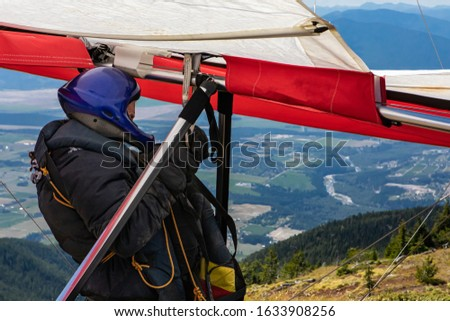 Hang-glider pilot in special clothing and gears preparing and checking his paraglider. A Deltaplan pilot about to launch #1633908256