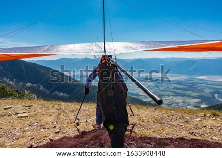 Man with hang-glider running for taking off the ground at the top of mountain hill. Paraglider ready for a flight. A Delta plane pilot about to launch #1633908448