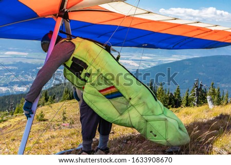 Man with hang-glider getting ready to fly and checking his gears and equipment. A Delta plane pilot about to launch. Medium shot #1633908670