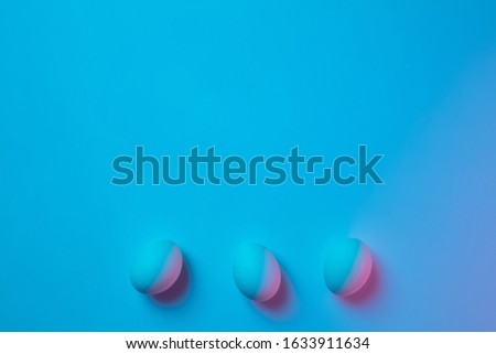 Egg hunt is coming. Easter traditions, pink-blue colored eggs on blue background, neon light top view, copyspace for ad. Concept of holidays, spring, celebrating, food and sweets, family time. #1633911634