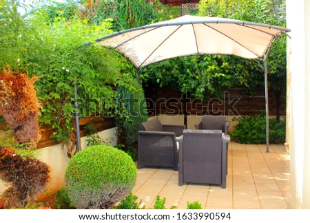 View of a summer holiday destination with armchairs and a parasol Royalty-Free Stock Photo #1633990594