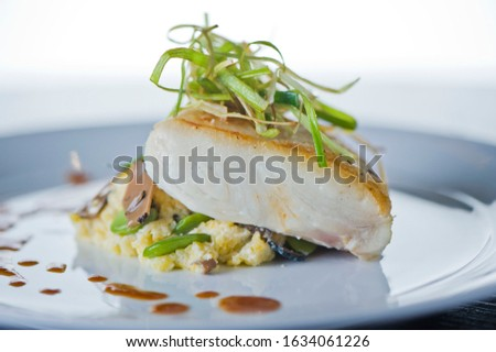 Halibut Fish Filet, plated on white plate and served with sauteed vegetables and topped with onions. Classic American restaurant favorite.