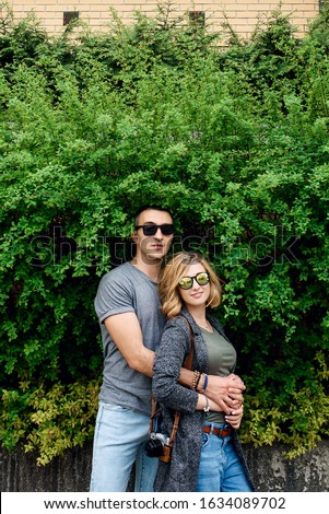 Love story in the summer. Portrait of a couple in love on a background of green bushes. They hug