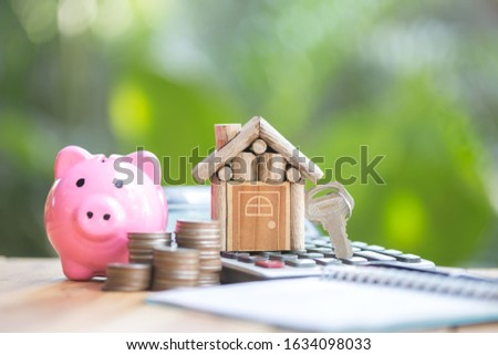Key house, is placed on the calculator. planning savings money of coins to buy a home concept for property, mortgage and real estate investment.to buy a house. #1634098033
