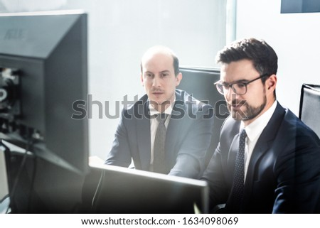Image of two thoughtful businessmen looking at data on multiple computer screens, solving business issue at business meeting in modern corporate office. Business success concept. #1634098069