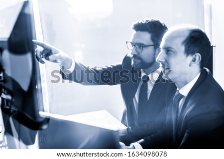 Image of two thoughtful businessmen looking at data on multiple computer screens, solving business issue at business meeting in modern corporate office. Business success concept. Blue toned. #1634098078