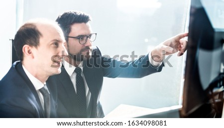 Image of two thoughtful businessmen looking at data on multiple computer screens, solving business issue at business meeting in modern corporate office. Business success concept. #1634098081