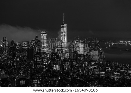 New York City skyline with lower Manhattan skyscrapers in storm at night. Black and white image.