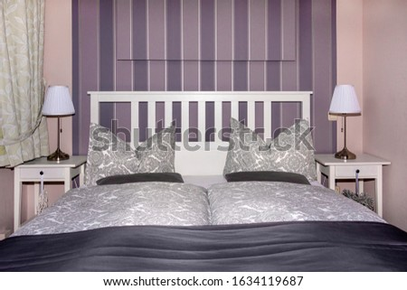 Hotel room with comfortable king size country style bed, stylish decoration, table lamp, striped wall, pillow, duvet blanket - concect vacation travel tourism business decor design comfort residence #1634119687