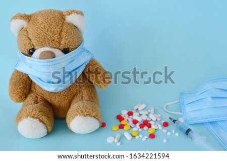 Toy bear in a medical protective mask, a syringe with a vaccine, multi-colored pills on a blue background. Protection, prevention of coronavirus, colds. Concept of illness, cold and flu.copy space. #1634221594
