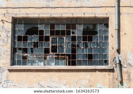 Old obsolete industrial building facade with broken windows #1634263573