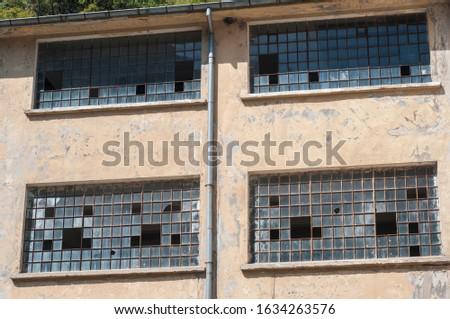 Old obsolete industrial building facade with broken windows #1634263576