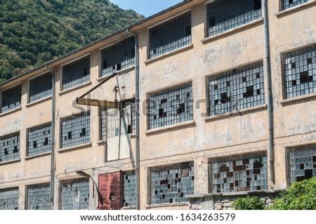 Old obsolete industrial building facade with broken windows #1634263579