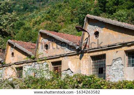 Old obsolete industrial building facade with broken windows #1634263582