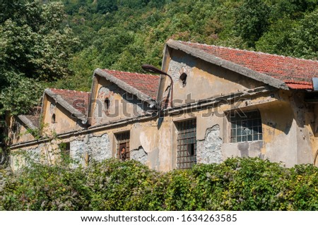 Old obsolete industrial building facade with broken windows #1634263585