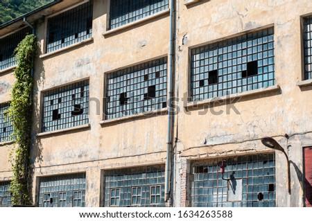 Old obsolete industrial building facade with broken windows #1634263588