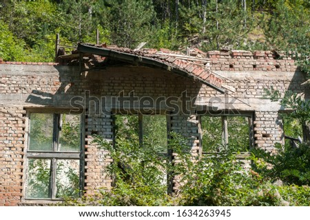 Old obsolete industrial building facade with broken windows #1634263945