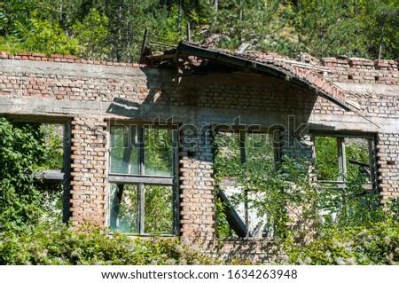 Old obsolete industrial building facade with broken windows #1634263948