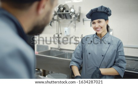 Two chefs in gray uniform are talking to each other while cooking in commercial kitchen, picture taken over man's shoulder