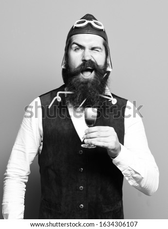 handsome bearded pilot or aviator man with long beard and mustache on smiling face holding glass of alcoholic shot in vintage suede leather waistcoat with hat, and glasses on blue studio background #1634306107
