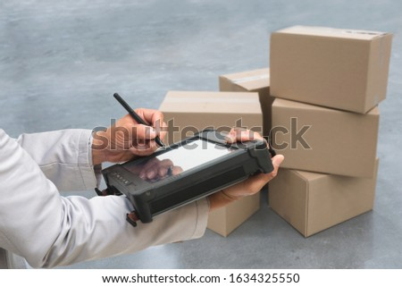 Closeup shooting hand of QC. worker with Rugged computers tablet and Bluetooth barcode scanner checking for logistics, Goods package boxes in warehouse. Royalty-Free Stock Photo #1634325550