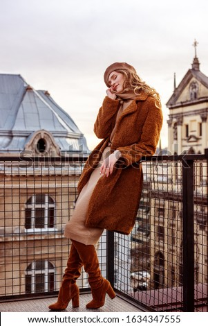 Outdoor full-length portrait of elegant fashionable woman wearing trendy monochrome beige, brown outfit: beret, dress, faux fur coat, high suede over knee boots, posing in European city Royalty-Free Stock Photo #1634347555