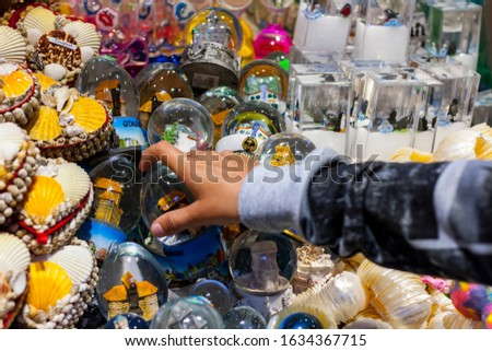 Child's hand grabbing snowglobe tourist souvenir from market stand with souvenirs from Gdansk and Sopot #1634367715