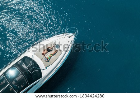 aerial view of couple enjoying sunbathing on the luxury yacht moving in the sea. Travel vacation Royalty-Free Stock Photo #1634424280