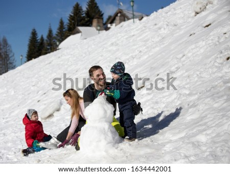 Parents with two boys playing on snow, making snowman. Winter family vacation #1634442001