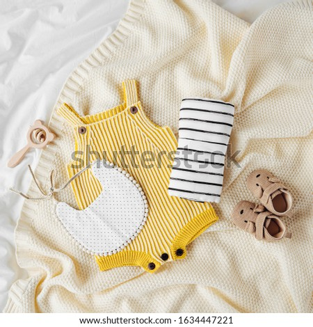 Yellow bodysuit, bib, baby boots and toy on knitted blanket. Set of  kids clothes and accessories  on bed. Fashion newborn. Flat lay, top view #1634447221