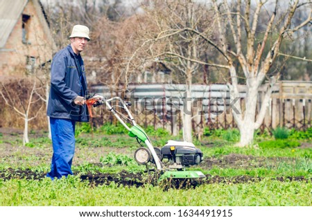 A man cultivates the land with a cultivator in a spring garden. #1634491915