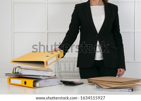 Business Documents concept : Employee woman hands working in Stacks paper files for searching and checking unfinished document achieves on folders papers at busy work desk office. Soft focus #1634515927