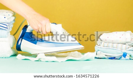 Woman hand pressing, ironing. Ironing newborn baby clothes with an electric iron #1634571226
