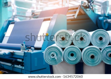 Rolls of industrial cotton fabric for clothing cloth textile manufacture on machine. Royalty-Free Stock Photo #1634572060