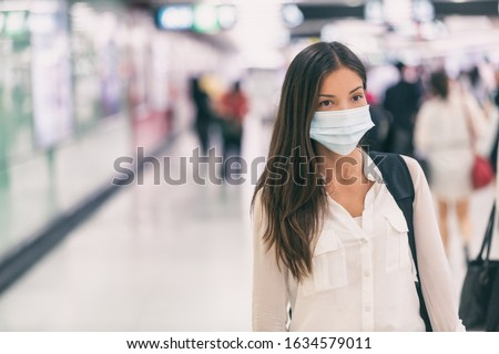 Coronavirus Asian woman walking with surgical mask face protection walking in crowds at airport train station work commute to hospital. #1634579011