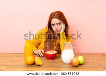 Teenager redhead girl having breakfast in a table unhappy and frustrated #1634581012