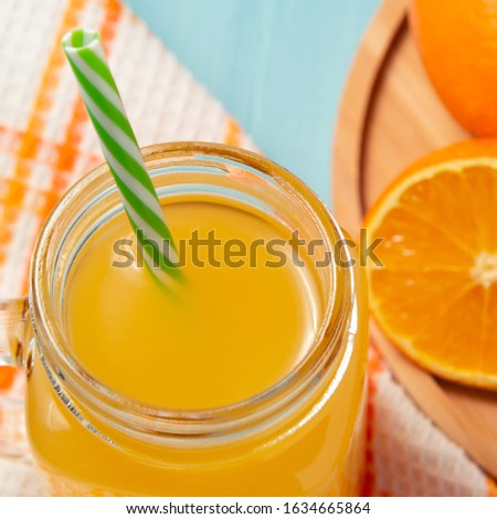 Homemade freshly squeezed orange juice in a mason jar, oranges and lime on wooden dish, square shape, closeup