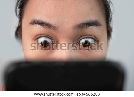 Asian woman staring at her smartphone screen all day. Focused on eyes. Mobile phone addiction. Royalty-Free Stock Photo #1634666203